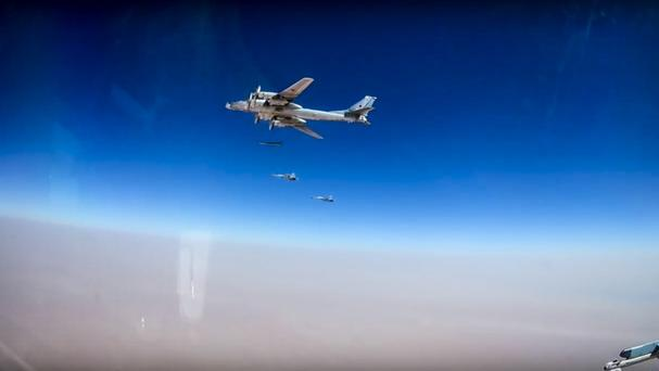 A Russian Tu-95 bomber launches cruise missiles on IS facilities in Syria (Russian Defence Ministry/AP)