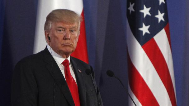 Donald Trump listens during a joint press conference in Warsaw (AP)