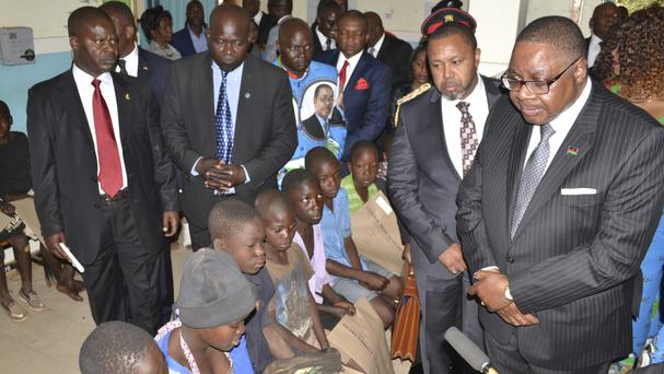President Peter Mutharika, right, meets injured children in Lilongwe (AP)