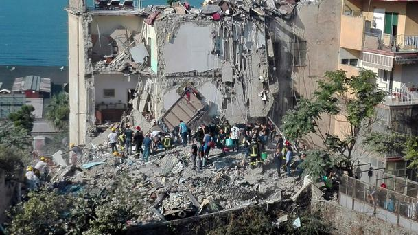 Rescuers work amid the rubble of a building that collapsed in Torre Annunziata, near Naples (Ansa/AP)