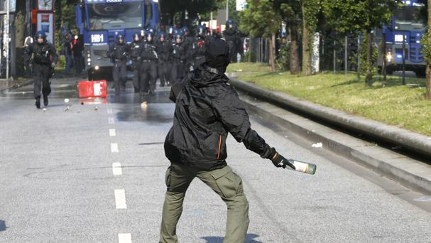 A demonstrator throws a bottle towards police on the first day of the G20 summit in Hamburg (AP)