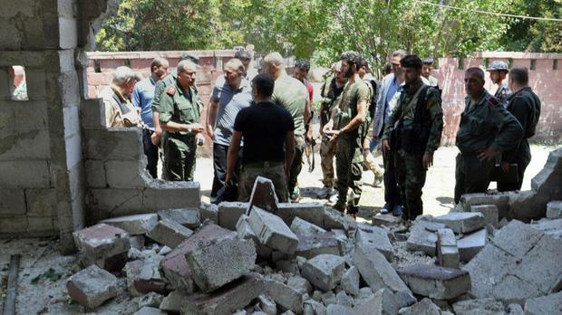 Officials gather after a suicide attack in Hama, Syria (Sana via AP)