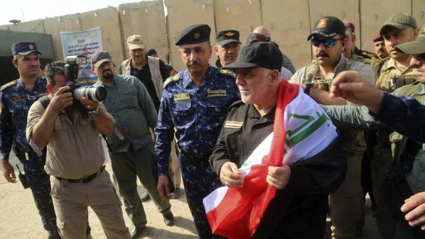 Haider al-Abadi holds a national flag on his arrival in Mosul (Iraqi Federal Police Press Office/AP)