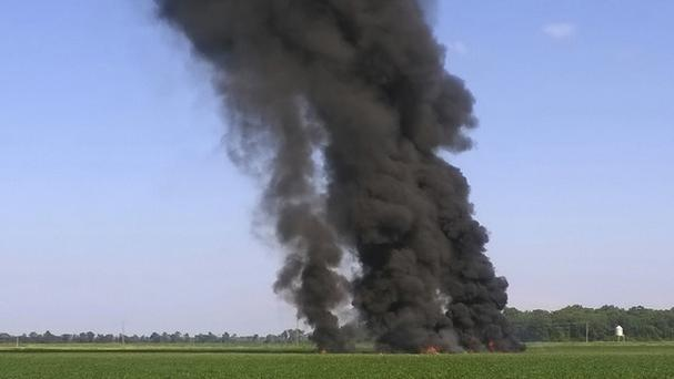 Smoke and flames rise into the air after a military transport airplane crashed in a field near Itta Bena (Jimmy Taylor via AP)