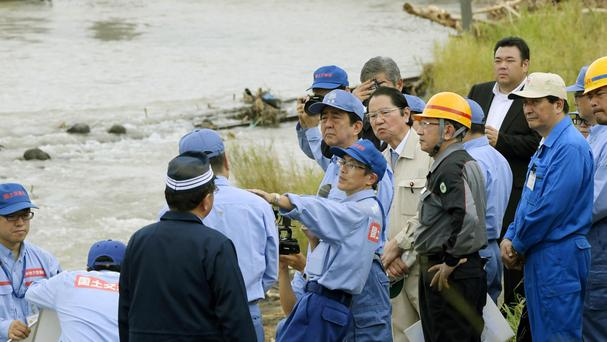 Japanese PM Shinzo Abe inspects damage by floods in south-west Japan (Nozomi Endo/Kyodo News/AP)