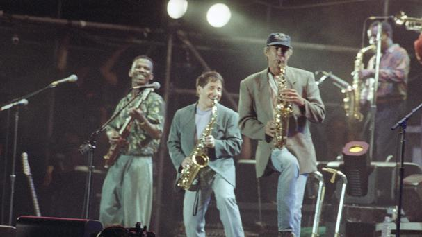 Paul Simon, centre, performs with Ray Phiri, left, and actor-comedian Chevy Chase on the saxophone in New York's Central Park in 1991 (AP)