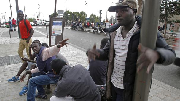 Migrants gather near a reception centre for migrants in Paris (AP)
