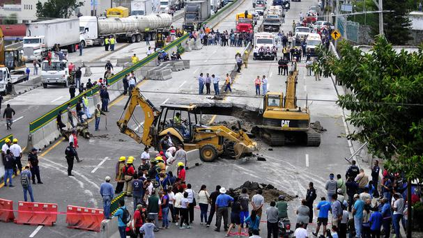 Rescue workers use heavy equipment to retrieve a vehicle from a sinkhole in Cuernavaca, Mexico (Tony Rivera/AP)