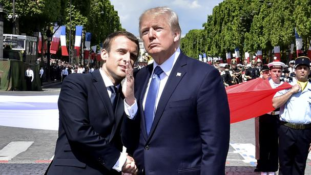 French president Emmanuel Macron, left, shakes hands with US president Donald Trump in Paris (Christophe Archambault/Pool via AP)