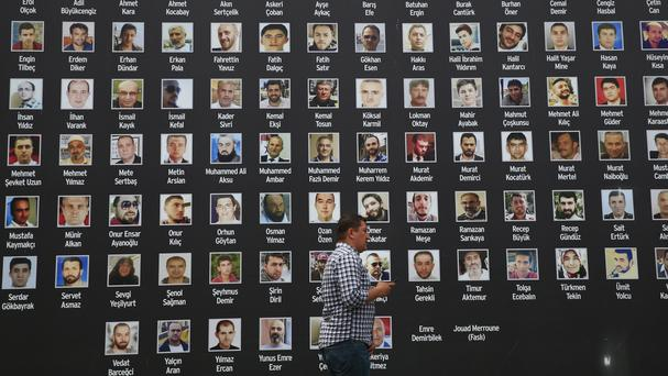 A wall of photographs of those who died fighting against the coup attempt last year (AP)