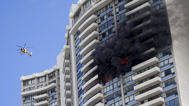 A Honolulu Fire Department helicopter flies near the burning Marco Polo apartment complex (Marco Garcia/AP)