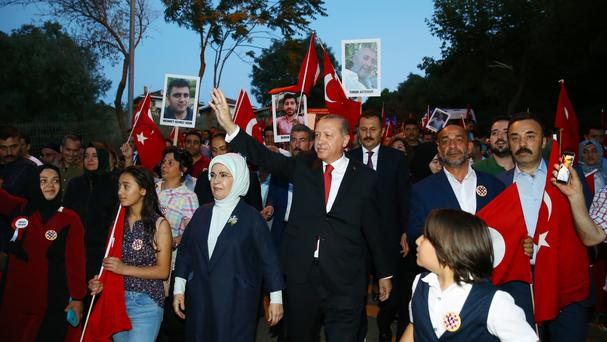 Recep Tayyip Erdogan, centre, waves to supporters as he marches with relatives of victims of the July 15, 2016 failed coup (Presidency Press Service/AP)