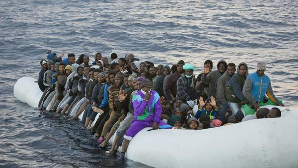 Migrants and refugees wait to be helped as they crowd aboard a rubber boat in the Mediterranean (AP/Emilio Morenatti)