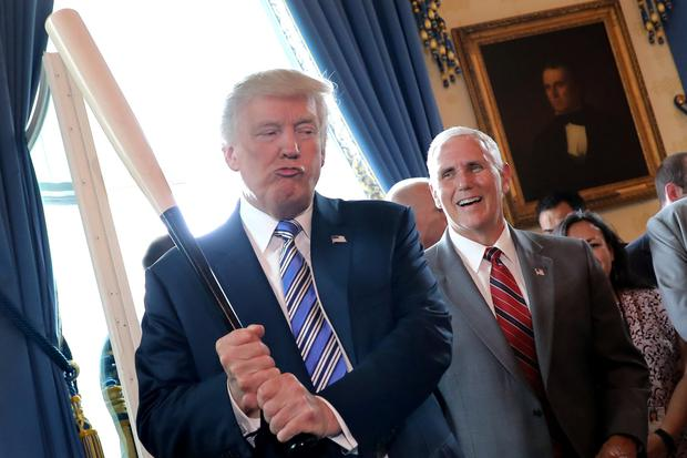 Vice President Mike Pence laughs as US President Donald Trump holds a baseball bat as they attend an event at the White House Photo: Reuters