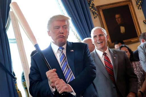 Vice President Mike Pence laughs as US President Donald Trump holds a baseball bat as they attend an event at the White House in Washington, yesterday. Photo: Reuters