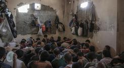 Suspected Islamic State members sit inside a small room in a prison south of Mosul. (AP)