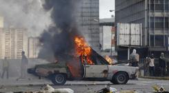 A car is set on fire during anti-government demonstrations in Caracas (AP Photo/Ariana Cubillos)