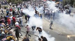 Palestinians run away from tear gas thrown by Israeli police officers