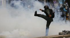 A Bolivarian National Guard officer kicks a tear gas canister during clashes with anti-government protesters in Caracas. (AP Photo/Ariana Cubillos)