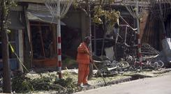 A worker clears up at the site of a suicide attack in Kabul, Afghanistan (AP Photos/Massoud Hossaini)