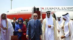Turkey's president Recep Tayyip Erdogan and his wife are greeted by the Emir of Qatar, Sheikh Tamim bin Hamad Al Thani (AP)