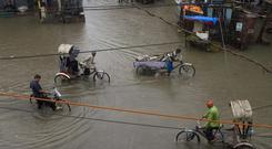 Indian rickshaw pullers wade through a water logged street following heavy monoon rain in Allahabad, India (AP Photo/Rajesh Kumar Singh)