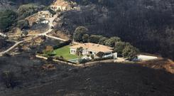Houses are surrounded by terrain scorched by wildfires near the village of Biguglia, Corsica (Raphael Poletti/AP)