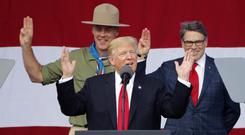 Mr Trump gestures as former boys scouts, interior secretary Ryan Zinke, left, and energy secretary Rick Perry, watch at the 2017 National Boy Scout Jamboree (AP)