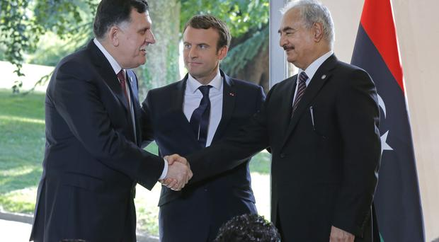 Libya's PM Fayez Serraj, left, and General Khalifa Hifter shake hands as French President Emmanuel Macron looks on (Michel Euler/AP)
