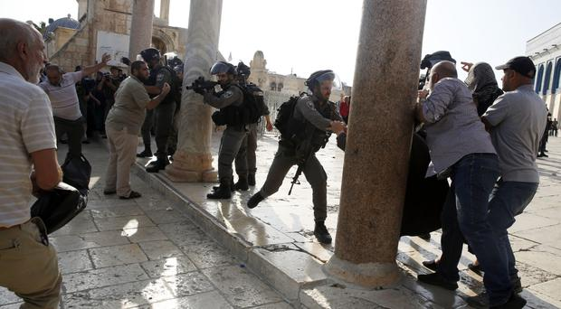 Israeli police stand guard as Palestinian women hold protest prayers outside the Lion's Gate in Jerusalem's Old City (AP)