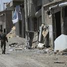 US-backed Syrian Democratic Forces fighters walk past destroyed shops in Raqqa (Hussein Malla/AP)