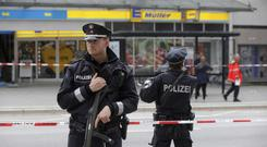 Police officers secure the area after a knife attack at a supermarket in Hamburg (AP)