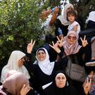 Palestinian women flash victory signs after prayers which were held outside the compound known to Muslims as Noble Sanctuary and to Jews as Temple Mount, just outside Jerusalem's Old City. Photo: Reuters
