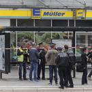Police officers outside a supermarket in Hamburg, Germany, where a man with a knife fatally stabbed one person and wounded several others (Markus Scholz/dpa via AP)