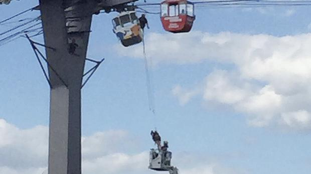 Firefighters rescue people from a cable car gondola across the river Rhine after it became stuck (dpa via AP)
