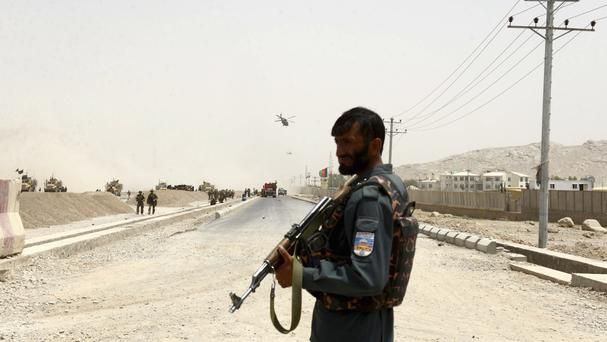 An Afghan policeman stands guard near the site where a suicide bomber struck at a Nato convoy in Kandahar (AP)