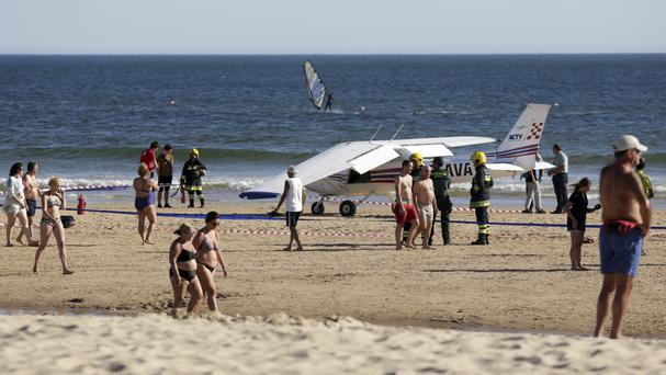 People walk past a small plane resting by the sea after an emergency landing at Sao Joao beach in Costa da Caparica, outside Lisbon. (AP)