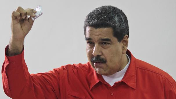 Nicolas Maduro shows his ballot after casting a vote for a constitutional assembly in Caracas, as he rejected claims that turnout figures were manipulated (Miraflores Press Office via AP)