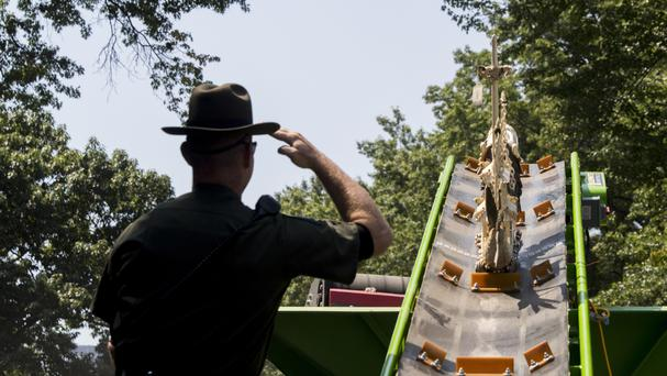 A New York State Environmental Conservation officer salutes as an ivory sculpture rolls up a conveyor belt into a crusher in New York's Central Park (Mary Altaffer/AP)