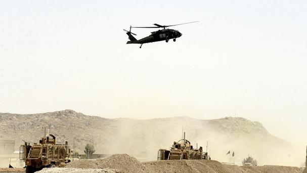 A US military helicopter flies over the site of a suicide bomb that struck a Nato convoy in Kandahar (AP Photo)