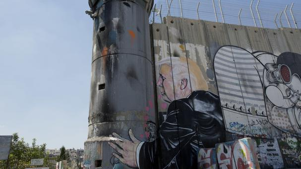 A mural resembling the work of elusive artist Banksy depicts US President Donald Trump kissing an Israeli army watchtower (Nasser Nasser/AP)