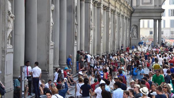 Tourists queueing to enter the Uffizi Gallery in Florence (Maurizio Degl'Innocenti/ANSA via AP)