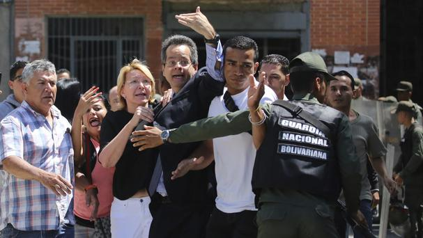 Venezuelan general prosecutor Luisa Ortega Diaz, third left, is surrounded by loyal employees as she was barred from entering her office by security forces (AP)