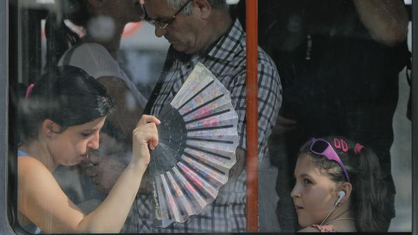 A woman uses a fan to cool herself and a child on a tram in Bucharest (AP)
