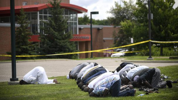 Mohamed Omar, left, the executive director of the Dar Al Farooq Center Islamic Centre leads afternoon prayers outside the police tape surrounding the centre