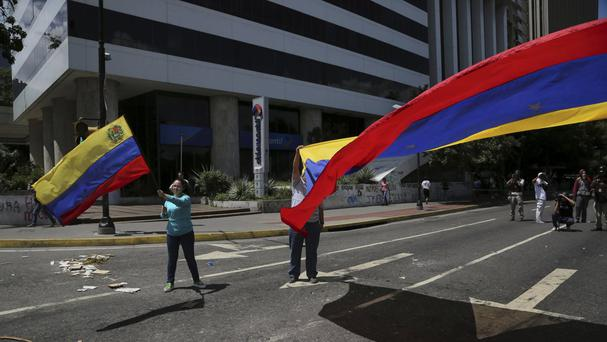Anti-government demonstrators wave Venezuelan flags during a protest against President Nicolas Maduro in Caracas (Wil Riera/AP)