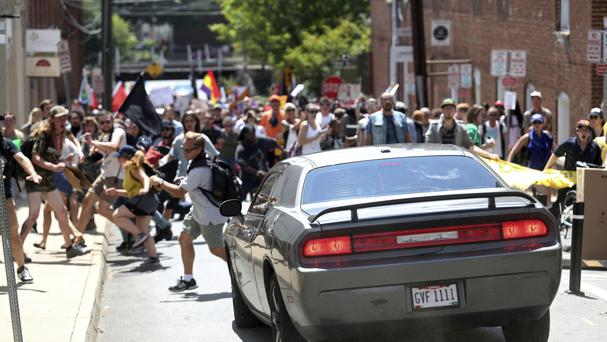 A vehicle drives into a group of protesters demonstrating against a white nationalist rally in Charlottesville (AP)