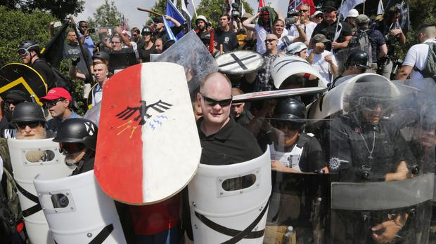 White nationalist demonstrators use shields as they guard the entrance to Lee Park in Charlottesville (AP)