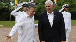 Mike Pence, right, is welcomed by Colombia's president Juan Manuel Santos in Cartagena (AP)