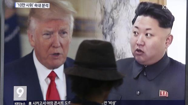 US President Donald Trump left and North Korean leader Kim Jong Un are shown on a television report in South Korea